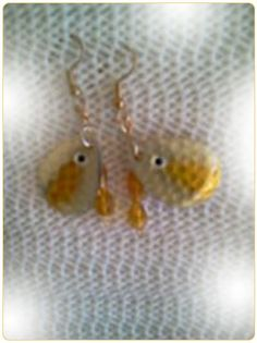 http://diginanchors.com/EarringsAlure_DangleHoneyBee - Dangling earrings handmade from fishing lures that is stamped out of pure brass and carefully hand painted. Honey Bee is painted honey and gold with an eye added to give it an eye catching look.Back is painted with 22k gold. Brilliant honey gold beads and crystals are added to enhance the appearance of the earrings.The unique earrings are 2 inches long and 3/4 inch wide.The earwires are surgical stainless steel and gold plated.