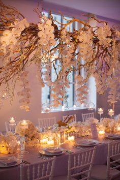 Hanging branches decorated with fresh flowers or even paper pompoms or lanterns can fill empty ceilings
