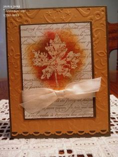 Stamp leaf in VersaMark on white cardstock. Sponge around leaf image. Stamp text on top of everything. Add bow, mats. She ran the orange mat through the Cuttlebug and punched the lower edge with a decorative punch. Nice!