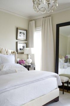 creamy bedroom with upholstered bed, espresso nightstand and oversized framed mirror