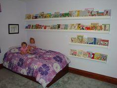 Full-wall bookshelf made of plastic rain gutters by Cheri.