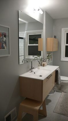 white penny tiles with dark grout. Ikea godmorgan vanity in white oak  light above mirror. grey paint.