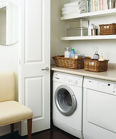 Fantastic hidden laundry room behind folding doors feauturing white front load washer and dryer and custom floating shelves and counter for folding and storage! Beautifuil wicker baskets and stainless steel storage containers combine style and funcion in this gem of a space hidden behind a gorgeous cream parsons chair and round mirror.