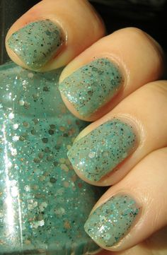 Galactic Gateway nail polish by BAM Nail Lacquer is a milky, light teal jelly packed with large and small silver hex glitter accompanied by various smaller blue, teal, and copper glitters. Opaque in 3 coats, this lacquer can be worn alone or layered for endless options.
