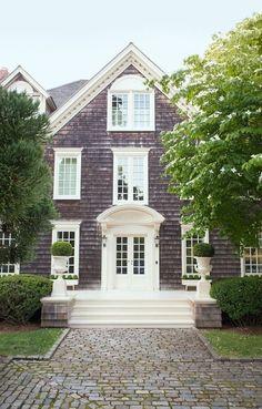 Shingle Style Architecture in Southampton: Gray weathered shingles, white trim, windows, door, and millwork. Cobble Stone walkway.   Veranda Magazine