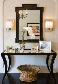 Chic foyer with black mirrored-top console table with wicker basket paired with black fretwork mirror flanked by polished nickel contemporary mirrored sconces.