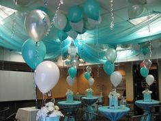 Confirmation Party decor.  Ceiling Draping and balloons create  fun decor in one of this seasons popular colours.  The same colours drape the cruiser tables to help complete the look.  Check out the mini chandelier at the centre of the ceiling fabric.  A personalized touch is added with large silver mylar letter balloons!