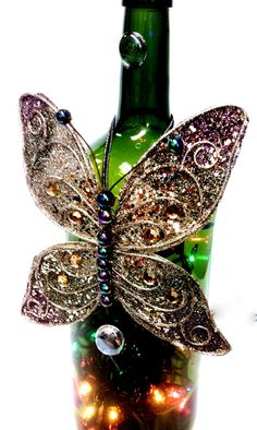 Using a glittery ornament, an old wine bottle and a stran of christmas lights this makes a beautiful gift...