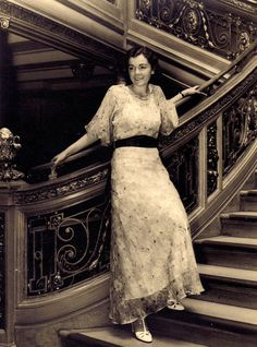 """A woman poses on the """"Grand Staircase"""" aboard RMS Olympic. Source: The Olympic Class Liners"""
