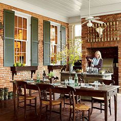 Antique Outdoor Farm Table | A long antique farm table surrounded by easily movable chairs can accommodate any crowd in this outdoor porch kitchen. | SouthernLiving.com