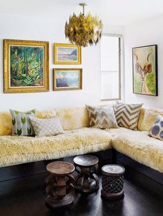 Living room with furry plush couch, framed nature paintings, Brutalist chandelier, and mixed throw pillows.