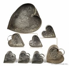 Seven tin heart shaped cheese strainers, together with a large tin mold