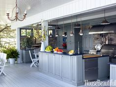 In Dianne Bernhard's Westport, Connecticut, kitchen, Plain & Fancy cabinets with Nantucket-style doors and blue-toned Caesarstone on top pick up the colors of the water just beyond the deck.