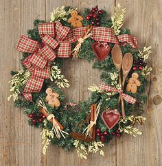 Kitchen Christmas wreath with cinnamon sticks, wooden spoons, gingerbread men and ribbon and berries.