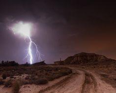 A lightning bolt strikes near a house in the Bardenas of Navarra, Spain.