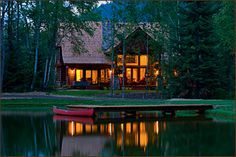 The vacation log home at sunset.  Looking out at the private lake that is so calm and the canoe standing ready for a candle light outing....