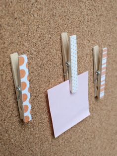 Clothespins with pushpins attached to the back. No more holes in the pictures on my bulletin board!