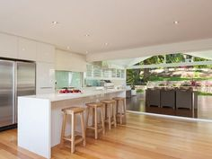 white coastal kitchen with louvers and centre islander and wide open area into the entertainment area