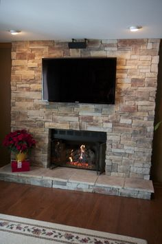 Ledge Stone Fireplace with TV located in Lake Zurich. Stone was installed directly over brick and the wall wired for the TV. Style of Ledge Stone is Mountain Stack.  www.northstarstone.biz  Call 847-996-6850