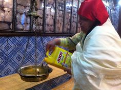 """A local woman fills a lantern with oil. Amos Cohen, a 19-year-old also from Hara Saghira (meaning """"Small Ghetto"""") who was giving out candles to pilgrims, said this year brought more people than 2011, when the pilgrimage was cancelled due to security fears."""
