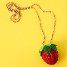 Turn a walnut into a strawberry necklace! You'll need paint, felt, and a chain.