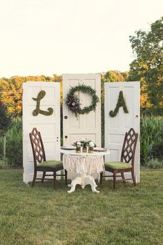 These vintage doors make the perfect backdrop for this sweetheart table.  outdoor wedding. rustic wedding. repurposed doors.  green wedding.  wedding ideas.  wedding wreath.