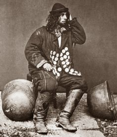 Kelderars are Romanian Gypsies. They made caldrons and baking trays on mobile anvils.  This young man sits with some of his work.  Notice the amazing detail on his jacket and also the hearts on his boots. 1865