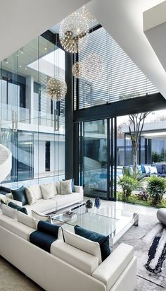 So many windows, so wonderful! What awesome lighting and tables and furniture as a whole. Good color theme. Contemporary living room.