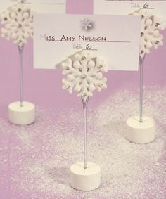 Let it snow, Let it snow, Let it snow with these snowflake place card holder wedding favors on your guests� tables.It�s easy to transform your reception hall into a winter wonderland with these unique snowflake place card holder wedding favors. Each features a white base and a single snowflake gracefully sitting atop a metal stand. Perfect for displaying winter wedding or event seating arrangements and for holding a photo or note in your guests� homes. Size:  4 �� tallDetails: These attractive …
