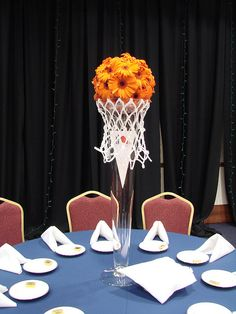 Basketball Bouquet Centerpiece -- Make a bouquet out of orange flowers and put the bouquet in a vase with a net from a basketball hoop around it.