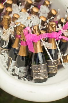These mini champagne bottles are festively decorated with vibrant pink ribbons and straws