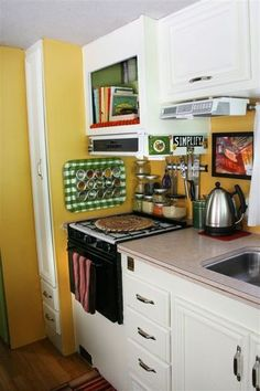 Tray on wall to hold magnetic spice jars!  Kitchen Spotlight: The Janssens' Incredibly Tiny RV Kitchen