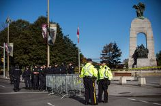 "Members of the Ottawa Police stand guard in front of the National War Memorial on Thursday, one day after a gunman killed a member of the Canadian Army Reserves. Following two shootings in Canada this week, Jeremy Keehn examines ""a shift in the global perception of the country in recent years as more warlike."" http://nyr.kr/1oBXWOl (Photograph by Andrew Burton / Getty)"