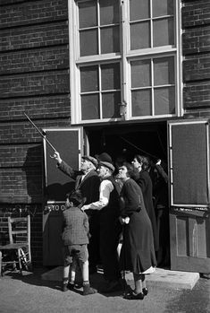 People at entrance of a public shelter watch enemy planes during a daytime raid in London during The Blitz of World War II in 1940. (George Rodger)