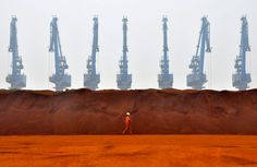 A worker walks past a pile of iron ore from Australia at a port in Tianjin on March 29, 2010. (Vincent Du/Reuters)