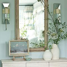 Nashville Idea House Bedroom Anteroom | Located between the bedroom and bath, this painted dresser is topped with sparkly mirrored scones and a large mirror to reflect all of the bedroom's natural light. | SouthernLiving.com