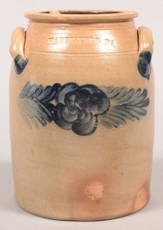 "Sold $ 300 Harrisburg, PA Poppy Flower Decorated 1 Gallon Stoneware Jar. Circa. 1860-1880. Cobalt blue slip with central poppy flower flanked by leaf design. Ovoid form with flared rim and applied ear handles. 9 1/4"" high. Condition: Rim chips."