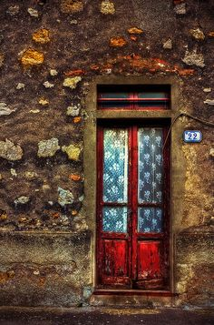 Love the stone walls around the red door. Tuscany, Italy
