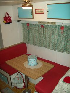 Dining Area of Vintage Travel Trailer-- New covered seats, curtains and paint.