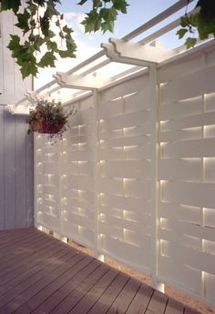 Here pergola elements have been added to the top of a privacy screen. The addition not only provides visual interest to the screen and deck, but is also functional as a place from which to hang lovely flowering baskets.