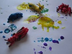 PLASTIC TOY PAINTING. Make tracks or footprints on the paper. Or just see what shaped splodges different toys make