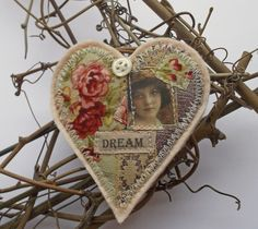 """Heart-shaped brooch, handmade with bits of vintage-style textiles, backed with wool felt, featuring the word """"Dream"""" and a vintage image of a young girl"""