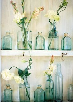 Such a great way to display flowers & brighten up a room. How cute do these shelves look filled with teal hued antique bottles? Love this.