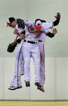 Nolan Reimold #14, Nick Markakis #21, and Adam Jones #10 of the Baltimore Orioles celebrates the Orioles 4-2 win over the Minnesota Twins during opening day at Oriole Park at Camden Yards on April 6, 2012 in Baltimore, Maryland.