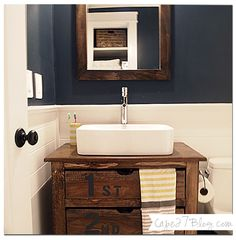 navy, yellow + white bathroom makeover with wide horizontal plank bead board sheets from Lowe's; wall paint is Benjamin Moore's Hale Navy