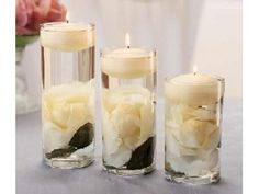 3 sizes of vases with flowers inside and floating candles