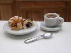 This plate of frosted croissants is perfect for tea time. There are 2 croissants on a ceramic plate. One is drizzled with vanilla glaze and