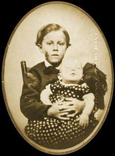 Young boy holding deceased infant sister. Salt print, c.1860