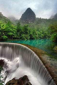 "Libo, Guizhou, China - Libo Zhangjiang Scenic Spot is located in Libo County, southern Guizhou, covering an area of about 273 square kilometers. Dubbed a ""green gem"", this national scenic area features wild karst forests interwoven with beautiful waterscapes and striking valleys and mountains. The area, together with the Maolan National Nature Reserve, an amazingly beautiful karst forest rarely seen in the subtropical zone along the same latitude, was named a World Natural Heritage site in 2007."