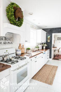 White painted kitchen cabinets, walnut butcher block countertops, chalkboard wall, white floors